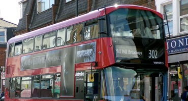 The number 302 Mill Hill Broadway bus at a stop outside shops.