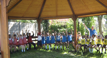 Group of children under a wooden canopy on a sunny day at Catholic School in Edgware.