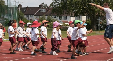 A group of children with a sports teacher exercising on a red running track at Mulberry House School West Hampstead.
