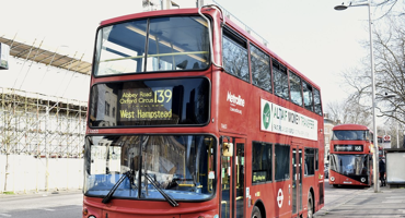 The 139 London red bus leaving a bus stop travelling to West Hampstead.