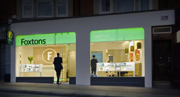 A man in a suit walking into Foxtons in West Hampstead in the evening.