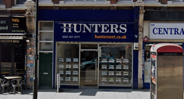 Shop front of Hunters Estate Agents branded in dark blue and yellow in West Hampstead.