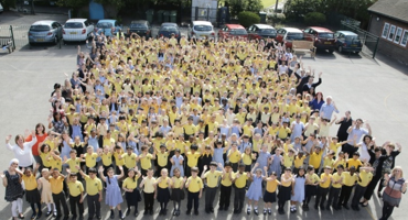 Group photo of over a hundred junior aged children all dressed in yellow uniform.