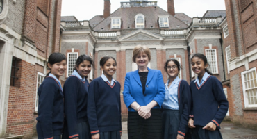 Group photo of students with the headteacher outside their Grade 2 listed campus.