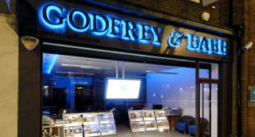 Exterior of Godfrey Estate Agents with a bright blue neon signage.