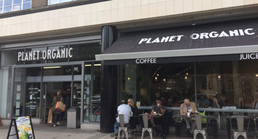 People sitting outside Planet Organic in Muswell Hill enjoying organic foods.