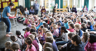 An assembly hall full of primary school children listening to a teacher.