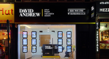 Exterior of David Andrew estate agents at night with the sign lit up.