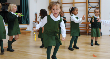 Young girls jumping up and down in the assembly hall at Sarum Hall School in Belsize Park.