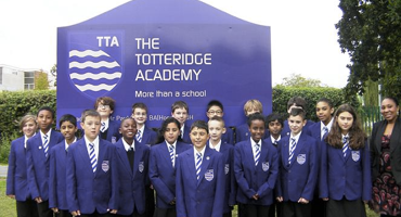 Group of secondary school pupils standing in purple uniform outside The Totteridge Academy.
