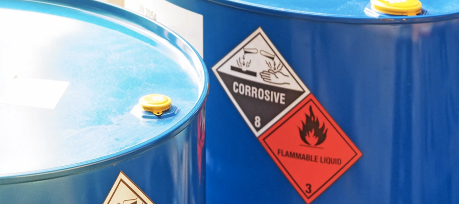 A blue steel drum holding corrosive and flammable liquid