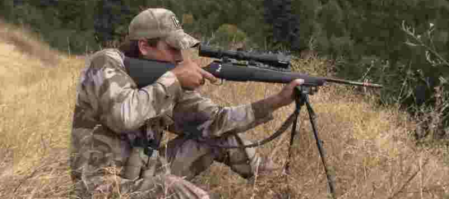 Man hunting with a rife dressed in camoflauge.
