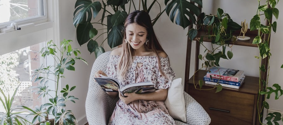 A girl sitting reading a book in a room full of house plants.