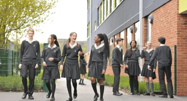 High school aged students in uniform walking and smiling on campus at The Archer Academy in East Finchley.