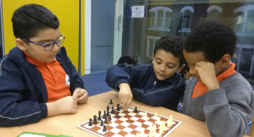 Three young boys playing chess at Kilburn Grange School.