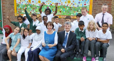 A group of mixed race children with the headteacher at Kingsgate Primary School in Kilburn.