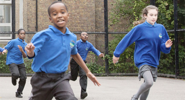 School children running in the playground at St Mary's Primary School in Kilburn.
