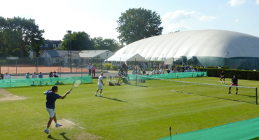 Tennis players playing on a grass court at Ealing Lawn Tennis Club.