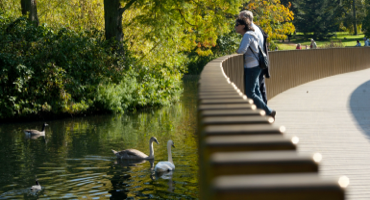 Couple standing on a bridge looking over the water at the Royal Botanic Gardens in Kew.
