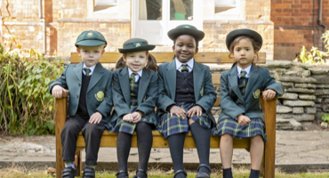 4 infant aged children sitting on the bench at St James Prep School in West London.