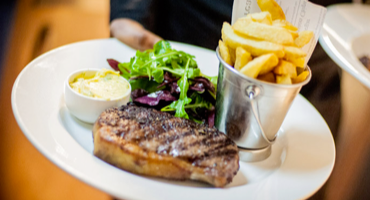 Waiter carrying a plate of steak and chips at the Rosendale pub in West Dulwich, London.