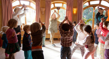 Children dancing in a circle with teachers at London Steiner School.