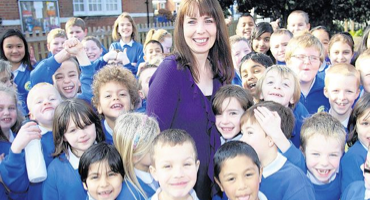 A group of children in uniform surrounding the head teacher at South Norwood Primary.