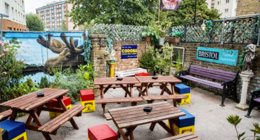 The Kenton Pub garden lined with benches and beautiful murals painted on the walls.