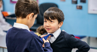 A boy making up a tie for their friend at The Lyceum School in East London.
