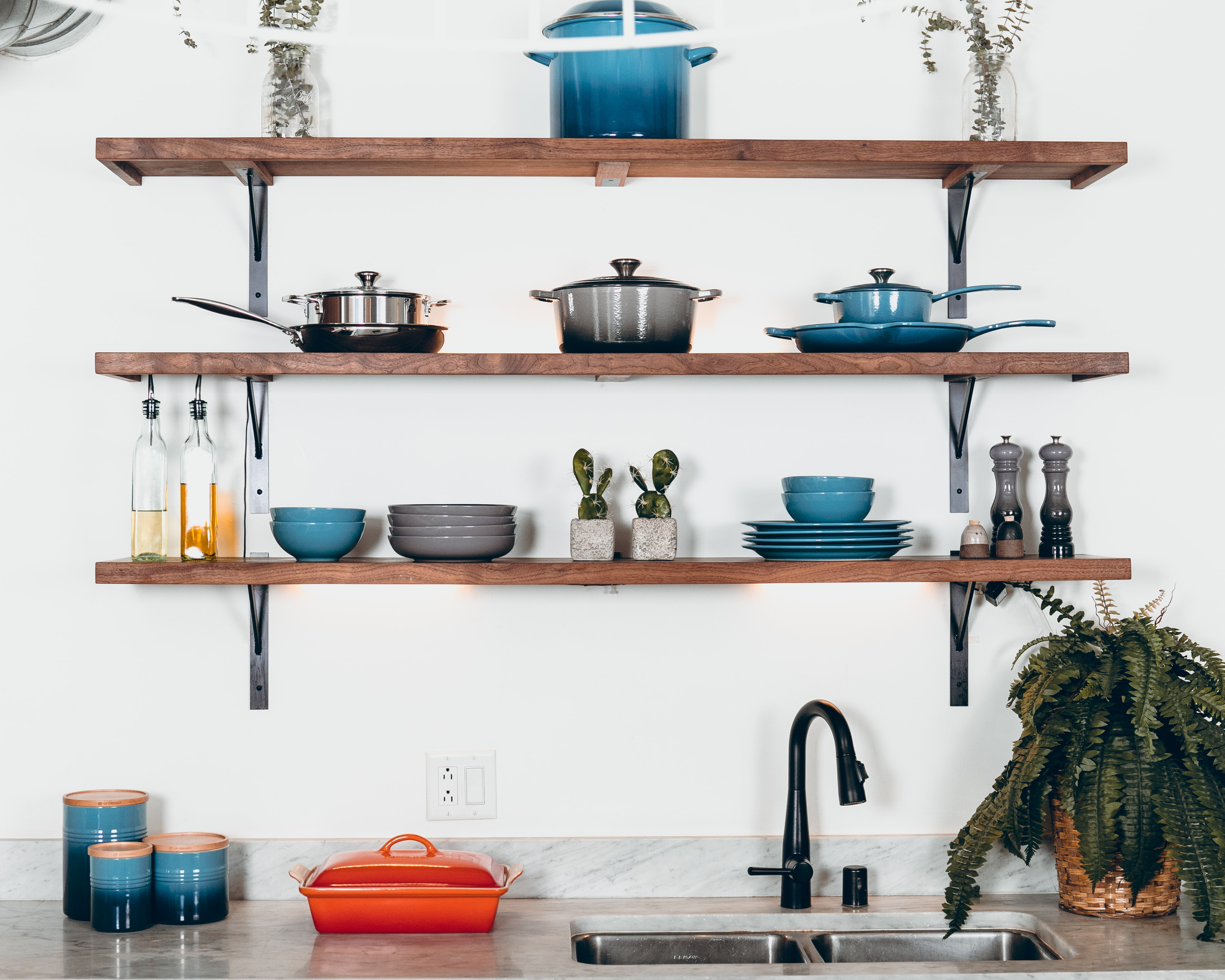 a kitchen counter and three shelves displaying colorful ceramic kitchenware
