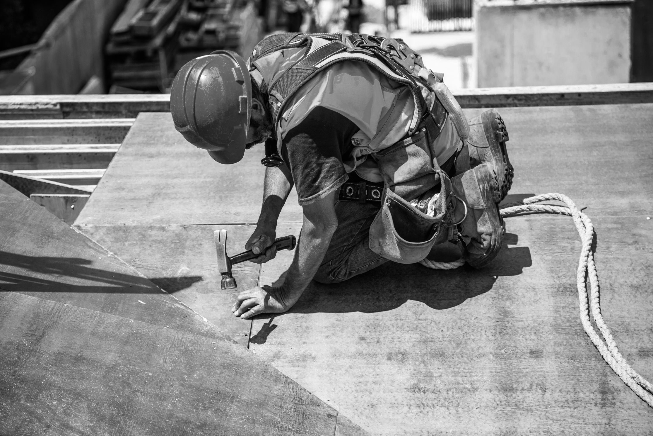 Black and white image of a construction worker, looking down and using tools.