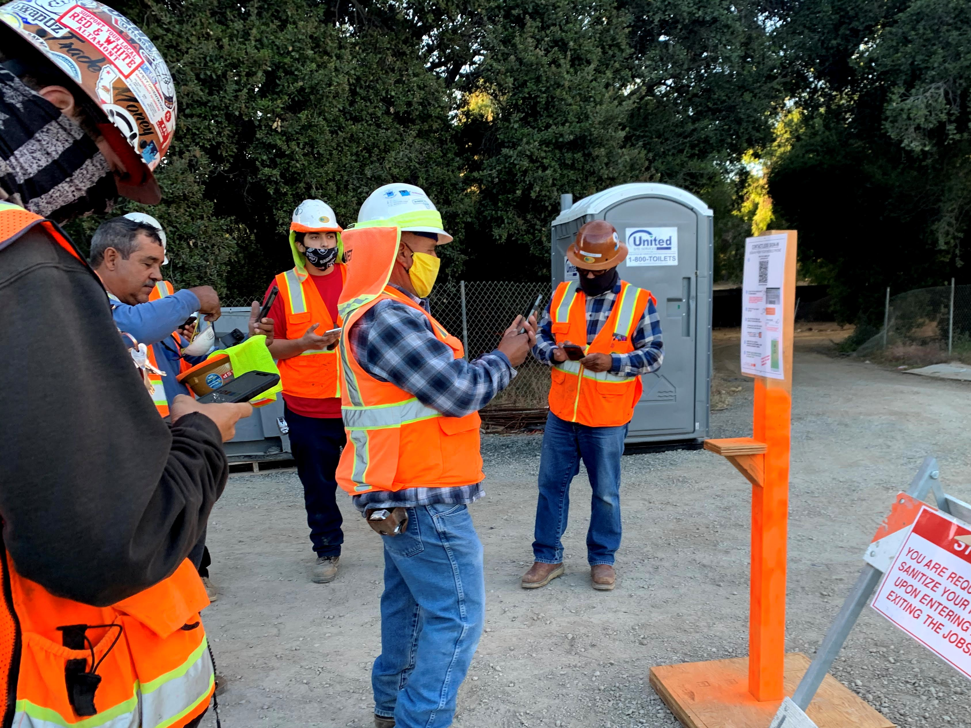 Construction workers using hand sanitizer.