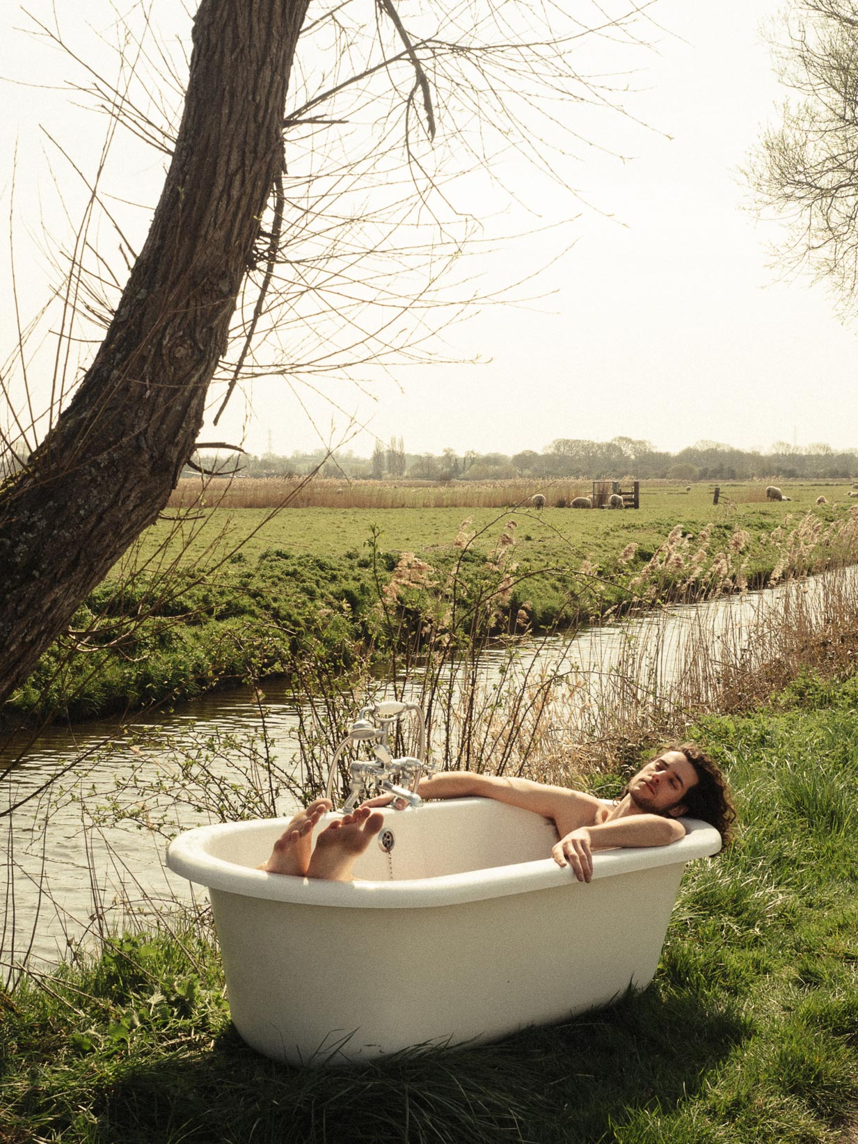 man sat in bath placed in a field