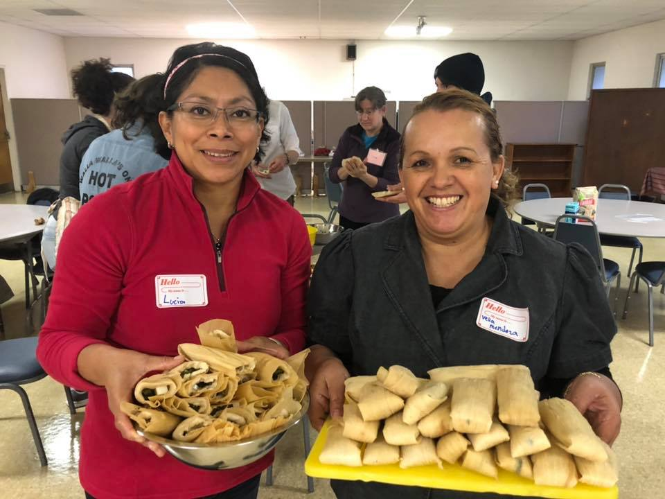 Two ladies holding tamale platters.