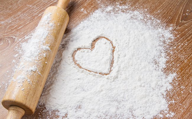 Flour on a cutting board with a heart drawn in it.