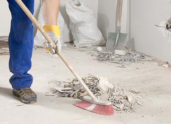 A man sweeping dust in a construction site.