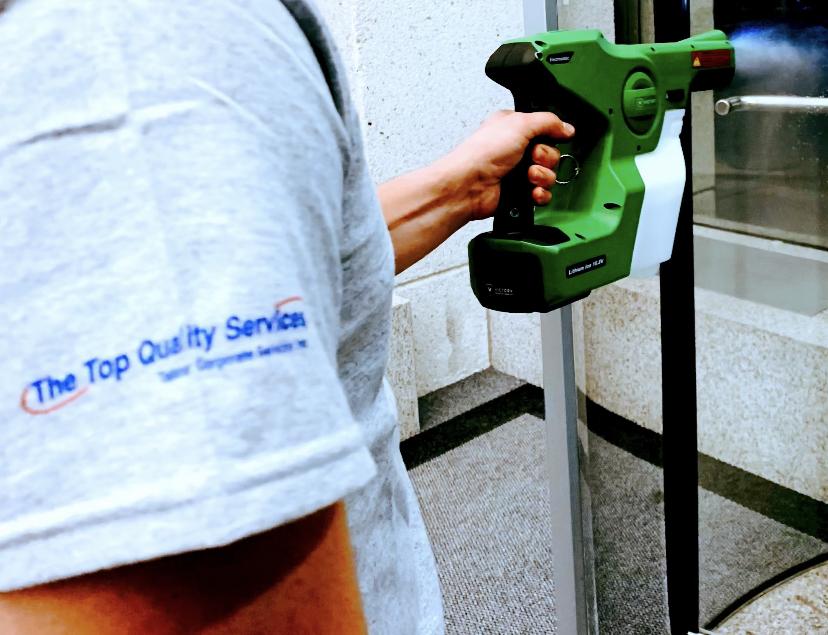 A man disinfecting a door with a disinfection spray gun.