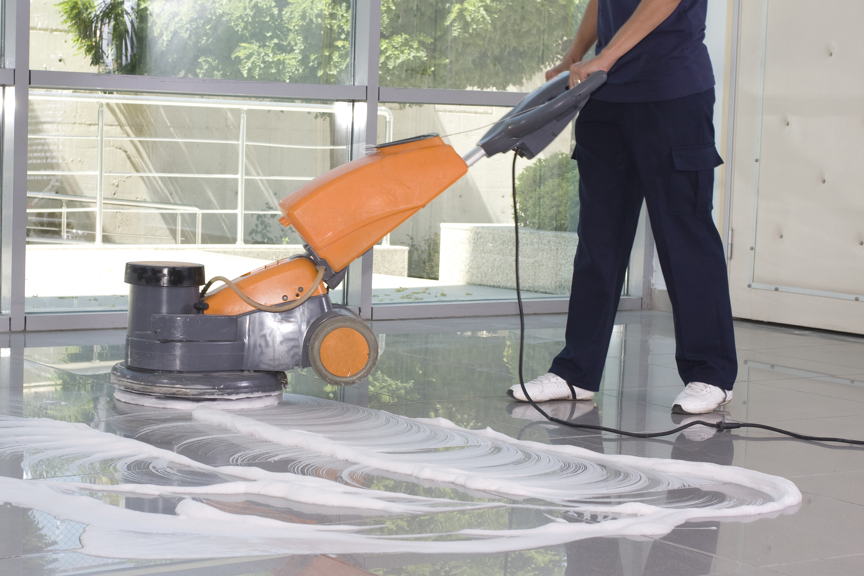 A person cleaning a floor with a floor cleaning machine.