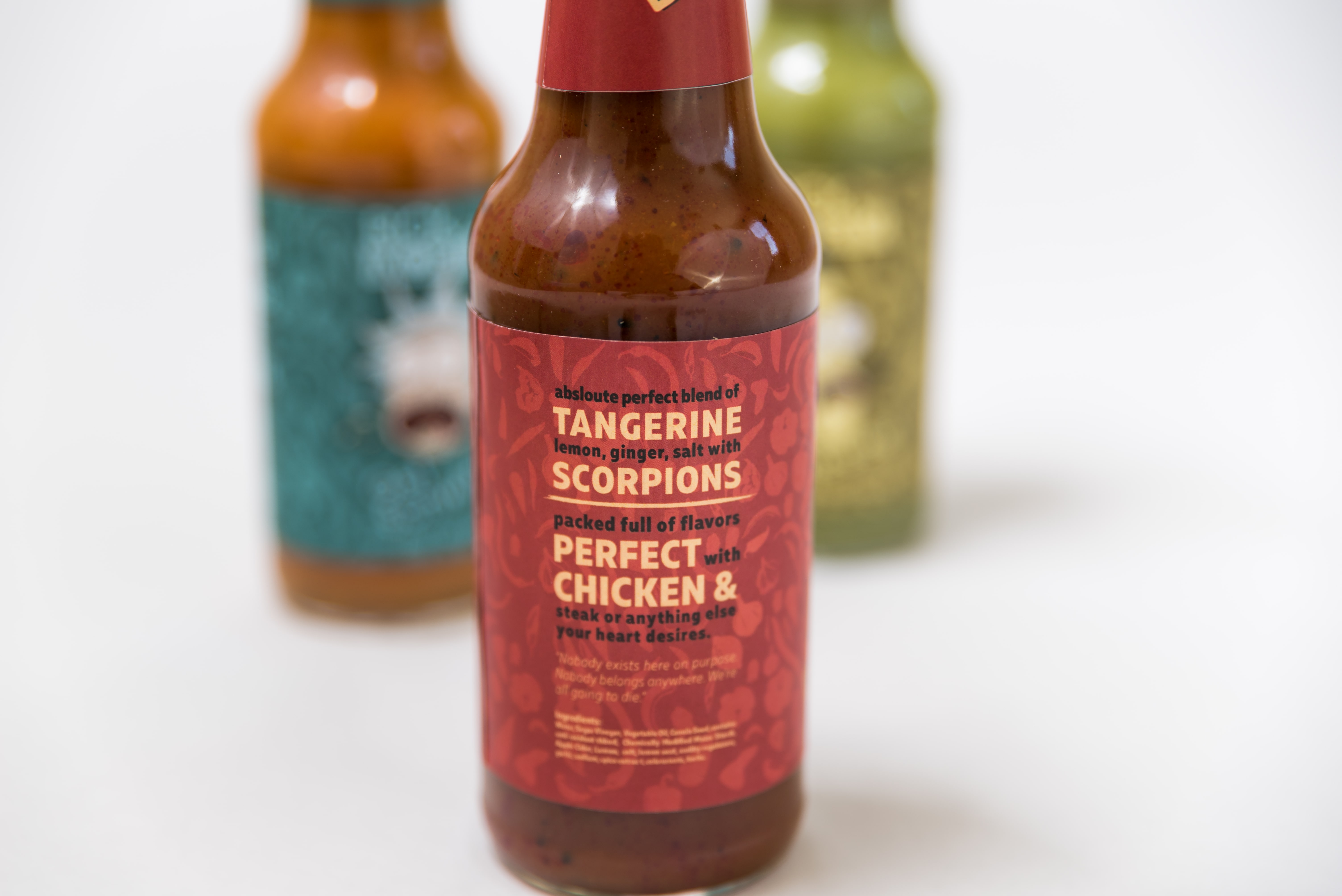 Three hotsauce bottles while focusing on the front bottle that shows the ingredients.