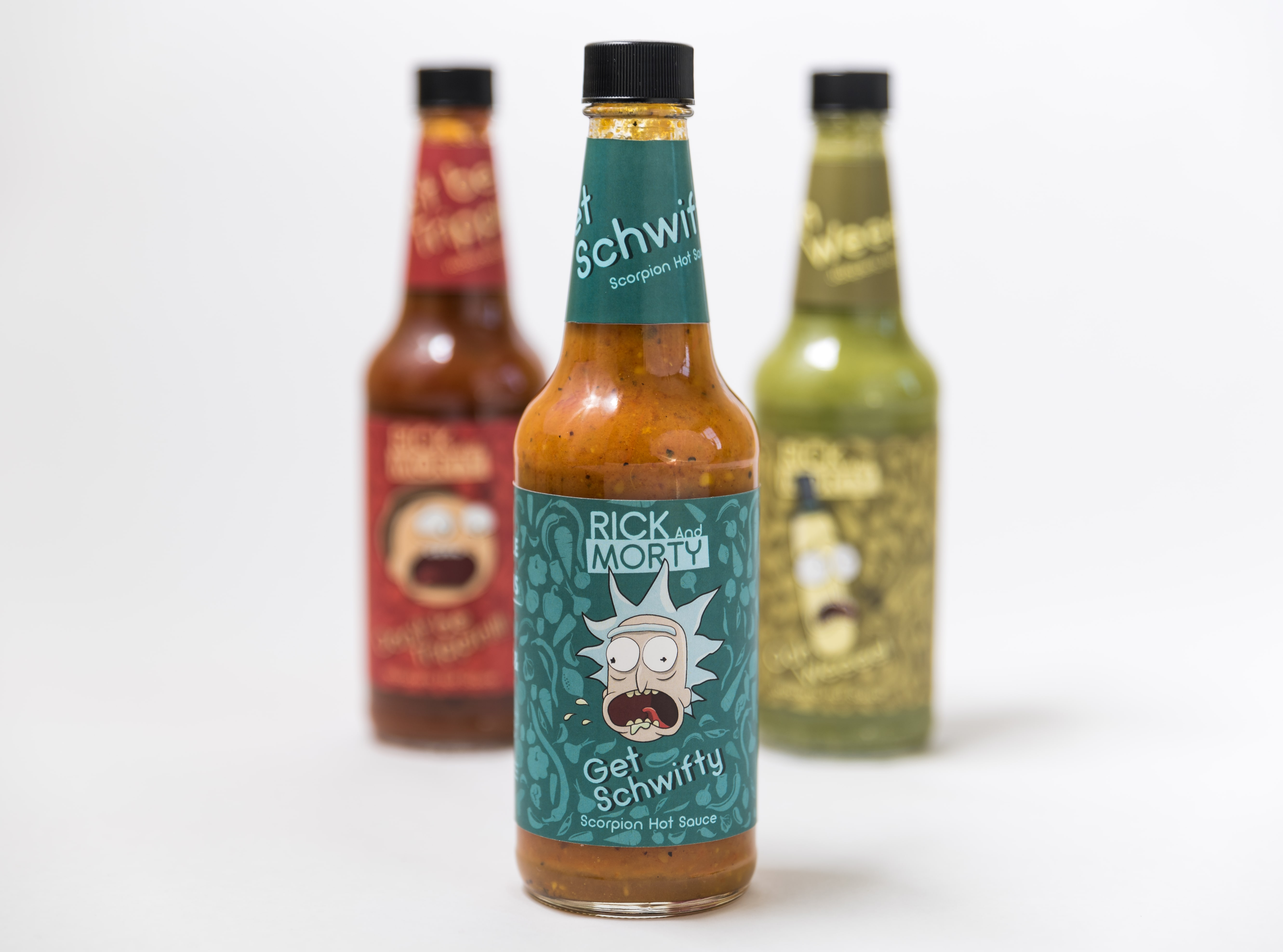 """Three hotsauce bottles while focusing on the front bottle that features Rick """"Get Schwifty"""" hotsauce."""