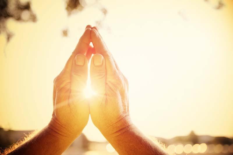 Hände zum Gebet gefaltet mit der Sonne im Hintergrund