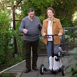 Patientin geht mit Orthoscoot und Begleitung spazieren