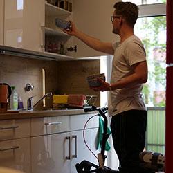 Junger Mann mit Orthoscoot räumt Küche ein