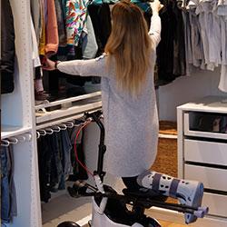 Junge Frau mit Orthoscoot am Kleiderschrank