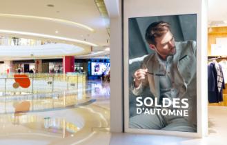 Dans une galerie commerciale, un écran assure une parfaite visibilité à un message publicitaire pour les soldes.