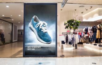 Un écran vertical affiche une publicité pour un magasin de chaussures
