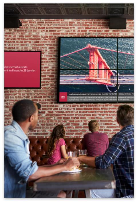 Les clients d'un bar tendance ont le regard tourné vers un écran d'affichage dynamique fixé au mur piloté par ADS.