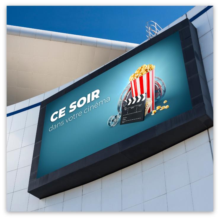Écran extérieur sur la façade d'un centre commercial affichant le programme du cinéma