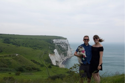 Man and woman standing with dog overlooking the White Cliffs of Dover and the sea.