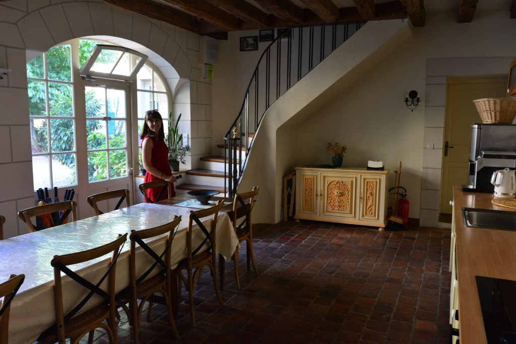 A kitchen with tile floors, a long table, and a winding staircase.